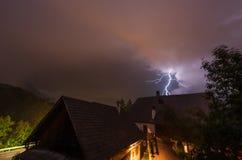 Blitzen Sie während eines Gewitters nachts hinter einem Landwirtschaftshaus Lizenzfreie Stockfotografie