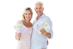 Blitzendes glückliches Paar ihr Bargeld Stockbilder
