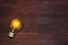 Blitzglasbirne auf dunklem hölzernem backgound Lizenzfreie Stockfotos