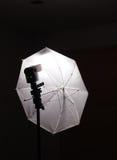 Blitzlichtgeschwindigkeitslicht auf Stand mit weißem Regenschirm Stockbild