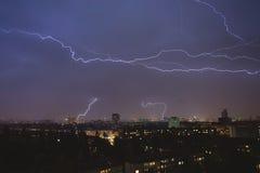 Blitzschläge über Nachtstadt während a Stockfotos