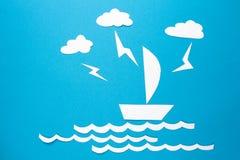 Blitzschläge im Papierschiffsorigami schwimmt auf Wellen Wolken und Blitz über Weißbuch versenden mit Segel auf blauem Hintergrun Stockbild