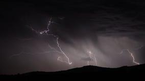 Blitzschlag über Gebirgszug mit Wolken Stockbild