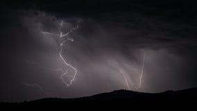 Blitzschlag über Gebirgszug mit Wolken Stockfotos