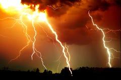 Blitzschlag auf dem dunklen bewölkten Himmel Orangen-, Gelbes und Rotesgetontes Bild Lizenzfreie Stockbilder