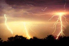 Blitzschlag auf dem dunklen bewölkten Himmel Orangen-, Gelbes und Rotesgetontes Bild Lizenzfreie Stockfotografie