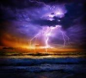 Blixt och storm på havet till solnedgången Arkivbild