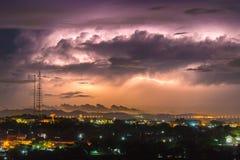 Blixt på himlen täckas med gråa moln i den regniga sen Arkivfoto