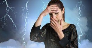 Blixtslag och stressad kvinna med det hållande huvudet för huvudvärk arkivbild