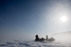 Blizzard. A pair of snowmobiles in a winter blizzard with blowing snow stock images