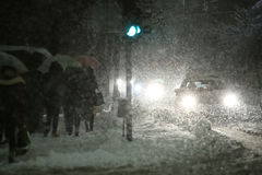 Blizzard in city. People with umbrellas walking in the street next to aggravated traffic due to strong snowfall Royalty Free Stock Photography