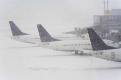 Blizzard on an international airport. Airplanes waiting in the snow Stock Images