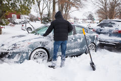 Blizzard. LONG ISLAND, NEW YORK - JANUARY 27,  2015:  Young man digging out and removing snow from cars after blizzard that hit the North East on Jan. 26 and 27 Royalty Free Stock Image