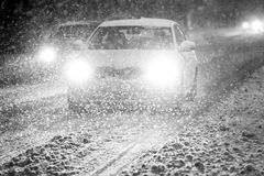 Blizzard at night bw. Cars driving on the road in the aggravated traffic due to strong snowfall Royalty Free Stock Photo