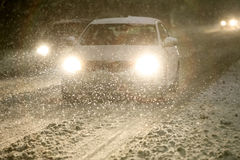 Blizzard at night. Cars driving on the road in the aggravated traffic due to strong snowfall Stock Photos
