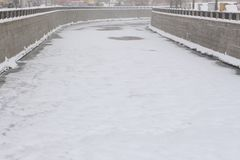 Blizzard over an urban canal, covered with ice. Blizzard over a city canal, covered with ice and powdered with snow Royalty Free Stock Images