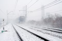 Blizzard and passing train. Snow falls. Railway tracks and vague silhouette of train Stock Image