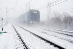Blizzard and passing train. Snow falls. Railway tracks and vague silhouette of train Royalty Free Stock Photo