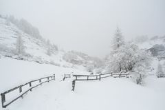 Snowbound field and wooden fence in alpine village stock images