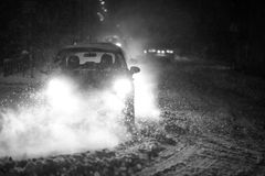 Blizzard in traffic bw. Cars driving on the road in the aggravated traffic due to strong snowfall Royalty Free Stock Photography