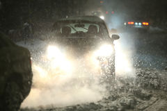 Blizzard in traffic. Cars driving on the road in the aggravated traffic due to strong snowfall Stock Image