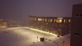 Blizzard in Tromso town. Heavy snowfall and blizzard over parking lot outside store building at dusk, Tromso, Norway stock footage
