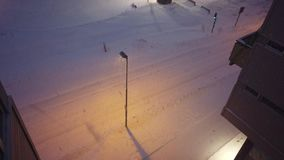 Blizzard in Tromso town. Heavy snowfall and blizzard over parking lot outside store building at dusk, Tromso, Norway stock video footage