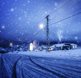 Blizzard in the village. Photo of blizzard in the village, snow falling on the house, night wintertime landscape, Christmastime greeting card, winter holiday stock photo