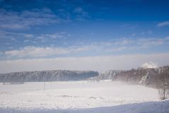 Blizzard in winter meadow. Winter meadow landscape with blue cky and clouds Royalty Free Stock Photography