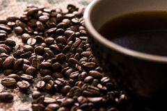Bllack-Tasse Kaffee nahe bei Kaffeebohnen auf Kaffeesack Stockbild