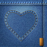 Bllue jeans heart on denim background. Royalty Free Stock Photos