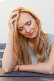 Blnd-Haarmädchen, das hinter der Tabelle und der Unterstützungskopfhand sitzt Lizenzfreies Stockbild