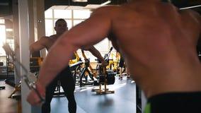 Bloß-chested Bodybuilder führt Kabel flye Übung in der Turnhalle vor dem Spiegel durch stock video