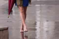 Bloße Beine der Frau mit Fersen und Regenschirm Lizenzfreies Stockbild