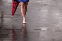 Bloße Beine der Frau mit Fersen und Regenschirm Lizenzfreie Stockfotos