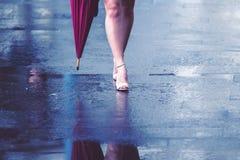 Bloße Beine der Frau mit Fersen und Regenschirm Stockbild