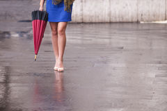 Bloße Beine der Frau mit Fersen und Regenschirm Stockfotos