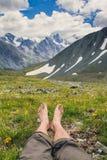 Bloße Füße auf einem Hintergrund von Bergen Stockbild
