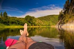 Bloße Füße auf Hintergrund von Fluss Stockbild
