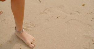 Bloße Füße beschichtet im Sand, der auf Strand geht stock footage