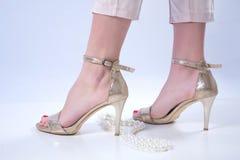 Bloße Füße der Frau in den goldenen hohen Absätzen und in der Perlenhalskette auf weißem Hintergrund stockbild