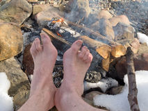 Bloße Füße, die an einem Lagerfeuer im Winter sich wärmen Stockfotografie