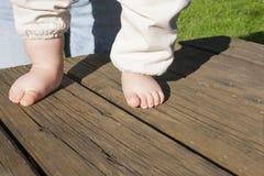 Bloße Füße eines Babys, das seine ersten Schritte tut Stockfotografie