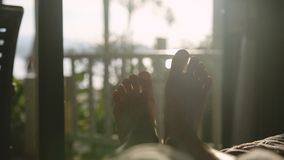 Bloße Füße im Bett am frühen Morgen in der Sonne mit schönem Blendenfleckeffekt Lizenzfreie Stockfotos