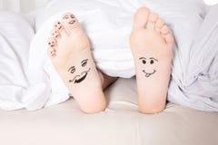 Bloße Füße mit smileygesichtern Stockfotografie