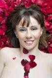 Bloße Frau der jungen Schönheit gelegt auf Rosen Lizenzfreies Stockbild