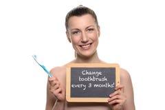 Bloße Frau, die Zahnbürste halten und leeres Brett Lizenzfreies Stockbild