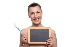 Bloße Frau, die Zahnbürste halten und leeres Brett Lizenzfreie Stockbilder