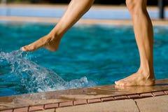 Bloße Frauenfahrwerkbeine durch das Pool Stockbild