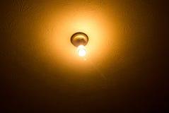 Bloße Glühlampe auf einer Decke Lizenzfreies Stockfoto